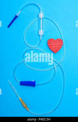 empty plastic dropper with needles and red heart on blue background, medical device - Stock Photo