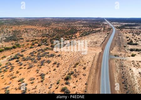 Aerial view of the great northern highway in red landscape, Eastern Goldfields, Western Australia | usage worldwide - Stock Photo
