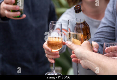 Friends toasting with drinks (lager and prosecco) at an outside social gathering - Stock Photo