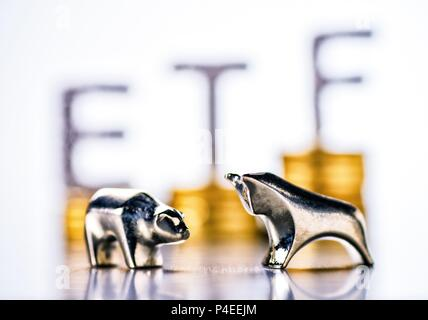 Bull and bear with stacks of coins and the letters ETF in the background | usage worldwide - Stock Photo