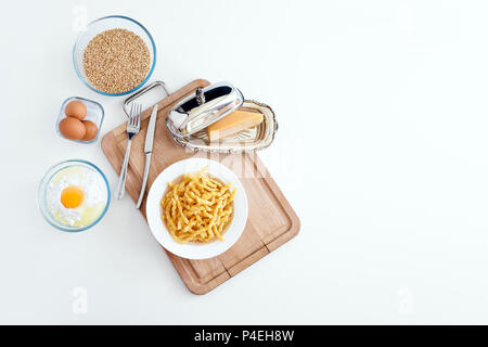 Italian tagliatelle pasta made by hand. Home made spaghetti. Italian food. Flour, egg, cheese, - cooking ingredients on wooden slate and white kitchen - Stock Photo