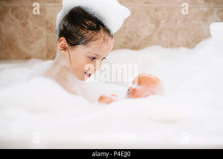 Girl sitting in a bubble bath with her doll - Stock Photo