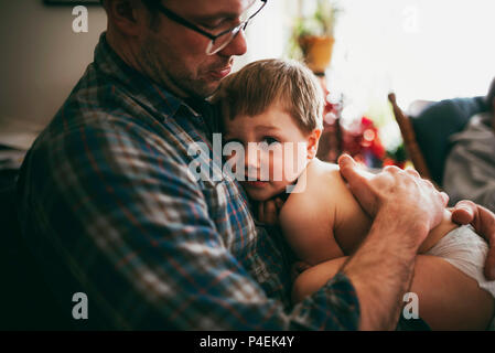 Father sitting on couch cuddling his son and kissing him on the head - Stock Photo