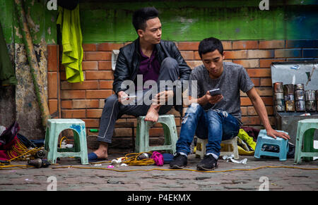 Hanoi, Vietnam - March 15, 2018: Street workers sitting on plastic chairs and waiting for customers - Stock Photo