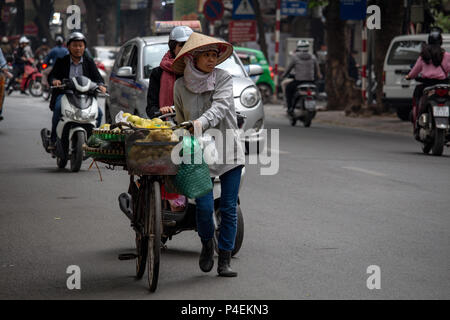 Hanoi, Vietnam - March 16, 2018: Senior lady selling fruits on the road with her bicycle - Stock Photo