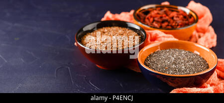 Super Foods - chia seeds, flax seeds and goji berries in three ceramic bowls - Stock Photo