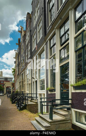 Facades of 17th century waterfront houses in Amsterdam. - Stock Photo