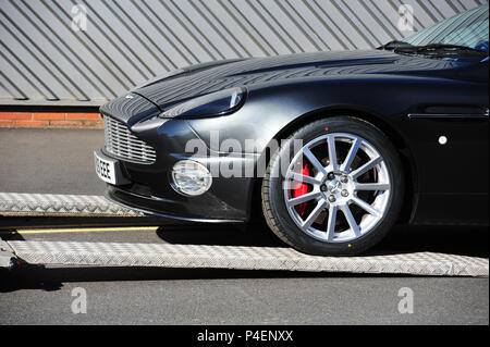 Aston Martin Vanquish S being loaded onto a sales collection trailer - Stock Photo