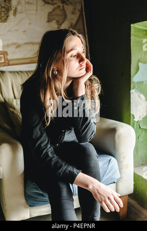 a woman in black denim clothing, jeans and a shirt, in a shabby location - Stock Photo