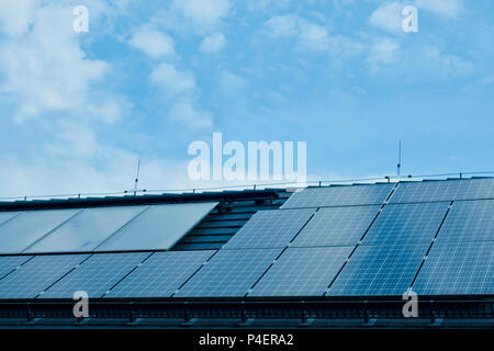 photovoltaic solar panel modules on the roof of a building to generate clean electric energy - Stock Photo