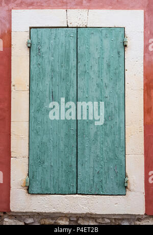 very old green painted shutters on window in medieval french house in provence - Stock Photo