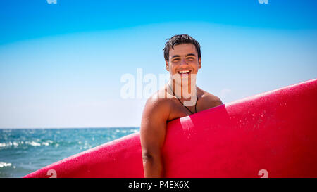 Portrait of a joyful smiling teen boy with red surfboard standing on the beach in anticipation of good waves, happy active summer vacation