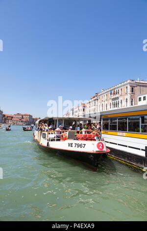 Passengers boarding a No. 2 Vaporetto waterbus at the San Marco stop on the Grand Canal, Venice, Veneto, Italy. Public transport, water bus - Stock Photo