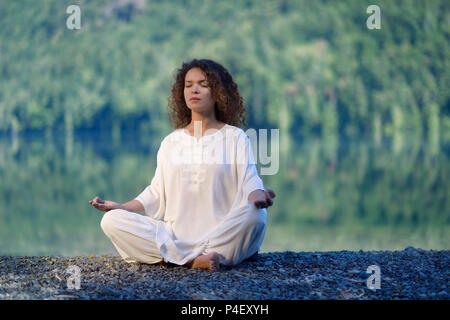 Young woman in white silk outfit meditating in the morning sunrise by the lake in the nature - Stock Photo