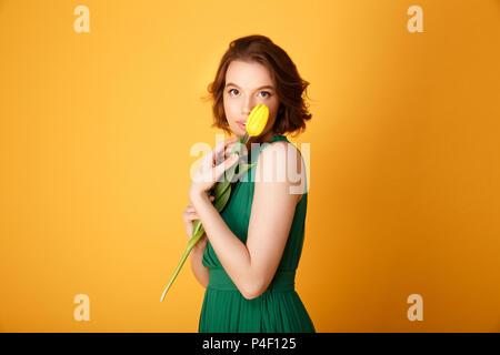 portrait of attractive woman in green dress holding yellow tulip isolated on orange - Stock Photo