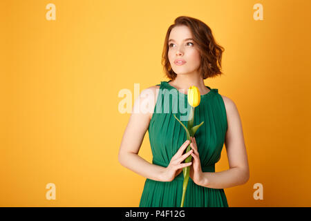 portrait of pensive woman in green dress holding yellow tulip isolated on orange - Stock Photo