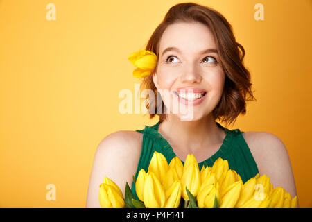 portrait of dreamy woman with bouquet of yellow tulips isolated on orange - Stock Photo