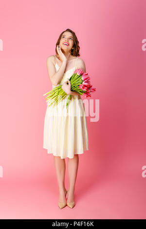 dreamy woman with bouquet of pink tulips isolated on pink - Stock Photo