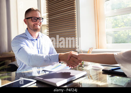 Smiling Young Businessman Shaking Hand With His Partner At Workplace - Stock Photo