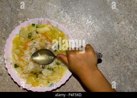 chicken soup with noodles and vegetables in plate. Childrens hold spoon with soup - Stock Photo