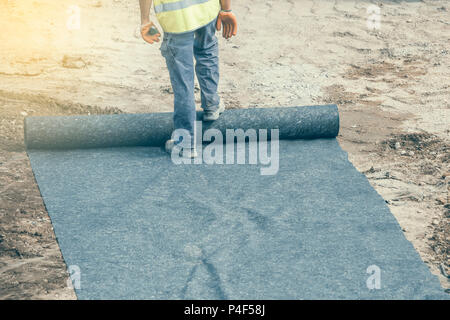 Installation of geotextile in between the sub base and base at construction site. Focus on legs. Vintage style. - Stock Photo
