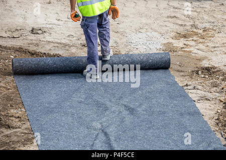 Installation of geotextile in between the sub base and base at construction site. Focus on legs. - Stock Photo