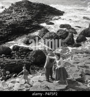 1950s, historical, mother, father and their young boy on the hexagonal rock columns at the famous Giant's Causeway, County Antrim, Northern Ireland. This unique coastal area of interlocking basalt columns, the result of an ancient volcanic fissure eruption is a natural wonder. - Stock Photo