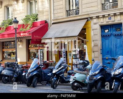 Motorcycles parked outside shops on Île Saint-Louis on the longest day of the year, Paris, France - Stock Photo