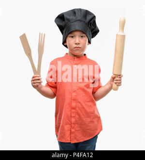 Dark haired little child wearing chef uniform with a confident expression on smart face thinking serious - Stock Photo