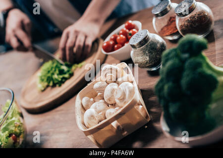 cropped shot of man cutting ingredients while cooking vegetable salad - Stock Photo