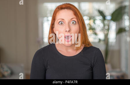Redhead woman at home scared in shock with a surprise face, afraid and excited with fear expression - Stock Photo