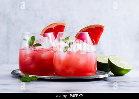 alcoholic cocktail Paloma of grapefruit and ice in glasses on a marble table . refreshing drink with lime juice - Stock Photo