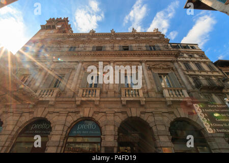 Verona, Italy – May 26, 2017: Beautiful residential building at Piazza Erbe in the Italian City of Verona with sunbeams - Stock Photo