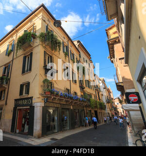 Verona, Italy – May 26, 2017: House with shops and blue flowers on a balcony in a pedestrian zone in Verona, Italy - Stock Photo