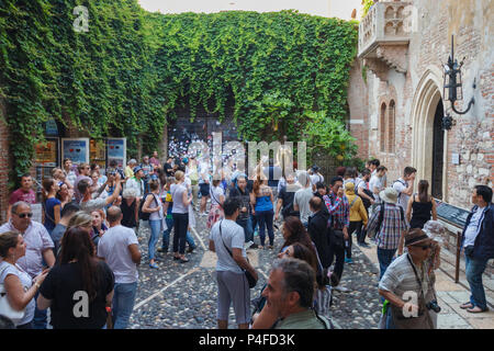 Verona, Italy – May 26, 2017: Crowed patio full of tourists visiting the statue under the famous balcony of Juliet's house - Stock Photo