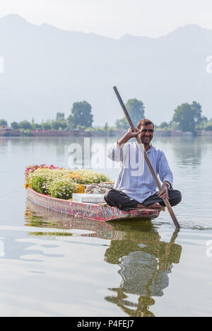 Srinagar, India - June 15, 2017: Unidentified kashmiri man selling flowers from his boat on the Dal lake in Srinagar, Jammu and Kashmir, India. - Stock Photo