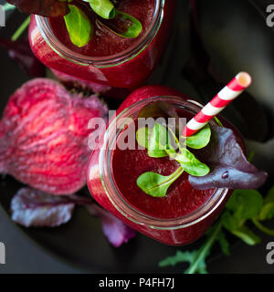 Fresh beetroot smoothie, beet, arugula and lettuce leaves on dark wooden background - Stock Photo