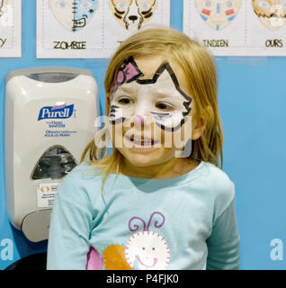 A three year old girl looking delighted with her new Hello Kitty face paint - Stock Photo