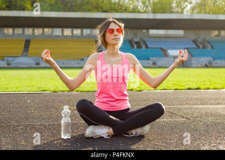 Young beautiful teenage girl practicing yoga in the stadium. - Stock Photo