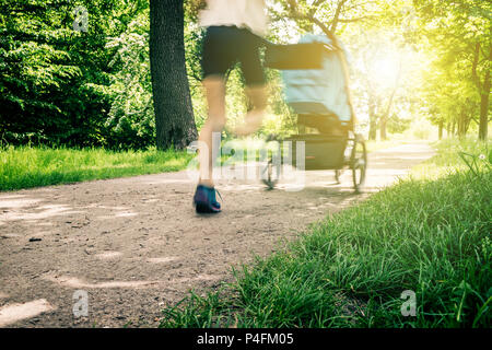 Running woman with baby stroller enjoying summer in park. Jogging or power walking supermom, active family with baby jogger, motion blur. - Stock Photo