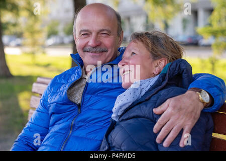 Mature european couple walking on street at good weather in spring. Lovers spanding time together. - Stock Photo