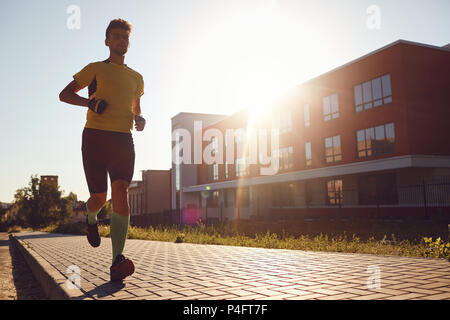 A sporty man runs through the streets of the city - Stock Photo