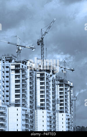 Blue Toned Image.Construction work of high-rise residential buildings.Active construction of the housing complex, with the working cranes . - Stock Photo