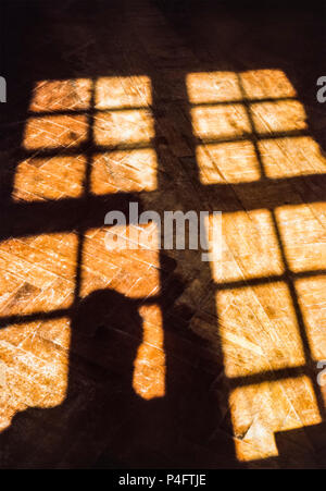 Shadows cast onto a varnished parquet floor by sunlight through a latticed window - Stock Photo
