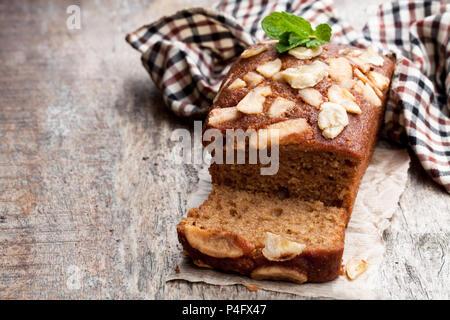 Homemade  banana loaf cake with fresh bananas on wooden table - Stock Photo