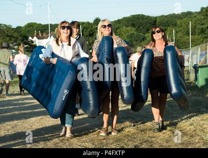 Heather Dockerty, April Beggs and Lorraine McAlister from Northern Ireland carry airbeds on site at the Isle of Wight festival at Seaclose Park, Newport. - Stock Photo
