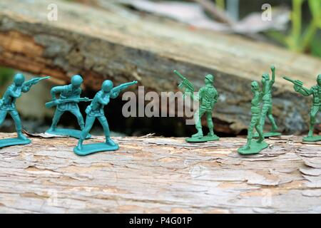 Plastic toy soldiers showing a battle scene - News Concept - Stock Photo