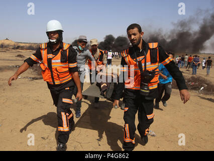 Gaza. 22nd June, 2018. Palestinian medics carry a wounded man during clashes with Israeli troops on the Gaza-Israel border, east of the southern Gaza Strip City of Khan Younis, on June 22, 2018. Credit: Khaled Omar/Xinhua/Alamy Live News - Stock Photo