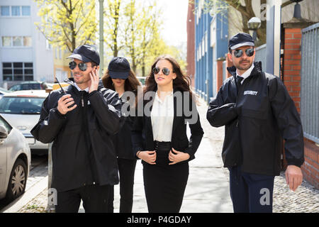 Portrait Of Young Female Celebrity With Bodyguards Walking On Sidewalk - Stock Photo