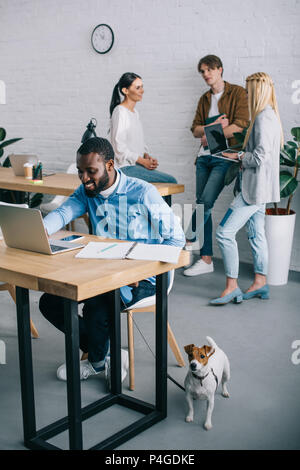 smiling african american businessman working on laptop and holding dog on leash and coworkers having meeting behind - Stock Photo